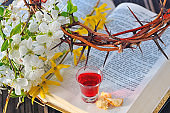 Communion cup with wine and bread on bible