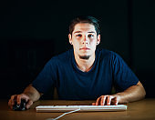 Young man working or playing on computer by night