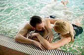 Loving couple relaxing at the spa in the pool