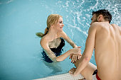 Loving couple relaxing in the spa by pool