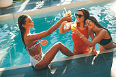 Young women drinking coctail and having fun by swimming pool