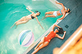 Three young women relaxing in the swimming pool
