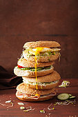 variety of sandwiches on bagels: egg, avocado, ham, tomato, soft cheese, alfalfa sprouts