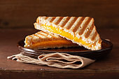 grilled cheese sandwich on rustic brown background