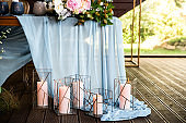 Festive table with long skyblue tablecloth decorated with candles in rustic candlesticks, peach color flowers on table