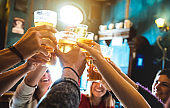 Group of happy friends drinking and toasting beer at brewery bar restaurant - Friendship concept with young people having fun together at cool vintage pub - Focus on middle pint glass - High iso image