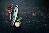 Fish. Raw Mackerel on a black wooden background. Top view. Free copy space.