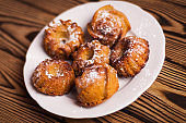 Baked cupcakes sprinkled powdered sugar on white ceramic dish on old rustic brown weathered table