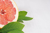 Colorfull juicy slice grapefruit and green leaves on white wooden board, macro, copy space.