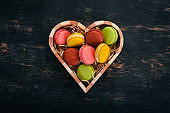 Macaroons colorful. Cake In a wooden box. Top view On a wooden background, Copy space.
