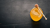 Honey in a jar on a black wooden background. Free space for text. Top view.