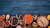 Set of Groats and Grains. Buckwheat, lentils, rice, millet, barley, corn, black rice. On a blue wooden  background. Top view. Copy space.