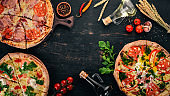 A set of pizza. On a black wooden background. Free space for text. Top view.