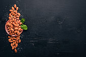 Almond nuts on a dark wooden background. Healthy snacks. Top view. Free space for text.