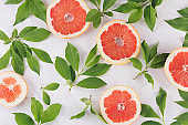 Juicy half grapefruits and fresh green leaves as decorative spring pattern on white wood background.