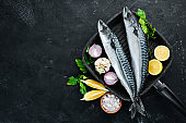 Raw mackerel on stone background. Fish and seafood. Top view. Free copy space.