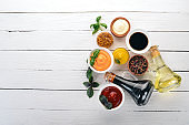 Set of sauces - Ketchup, mayonnaise, mustard, soy sauce, barbecue sauce, pepper and spices. On a white wooden background. Top view. Free space for text.