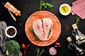 Raw chicken breast with spices and herbs. Barbecue. On a black stone background. Top view. Free copy space.