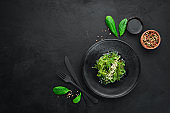 Seaweed salad in a black plate. Chuka wakame On the old background. Top view. Free space for your text.