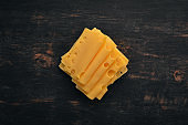 Yellow sliced cheese Maasdam. Top view. On a wooden background. Free copy space.