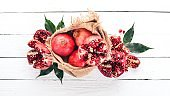 Fresh pomegranate in an old bag. On a wooden background. Top view. Copy space.