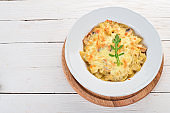 Farfalle pasta with cheese and mushrooms. On a wooden background. Top view. Copy space.