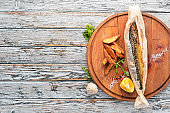 Baked mackerel fish in parchment paper. On a wooden board. Free copy space. Top view.