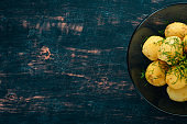 Boiled potatoes with dill in a bowl. On a wooden background. Top view. Copy space.