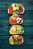 Set Burger, sandwich. with quail eggs, cucumbers and corn, salami and seafood. On a wooden background. Top view. Copy space.