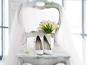 White shoes, shimmering pink veil and bridal bouquet with Calla lilies. Details of wedding ceremony.
