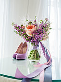 Bridal bouquet with peony roses, eustoma and other flowers. Colorful purple shoes. Traditional floral composition and modern trendy fashionable accessory for wedding ceremony.