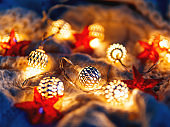 Christmas and New Year knitted background with light bulbs and red stars. Cozy holiday decorations.