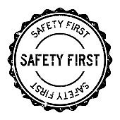 Grunge black safety first word round rubber seal stamp on white background