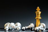 Gold king chess piece win over lying down pawn on black background