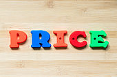 Color plastic alphabet in word price on wood background