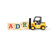 Toy forklift hold wood letter block A to complete word ADR (Abbreviation of Adverse drug reaction) on white background