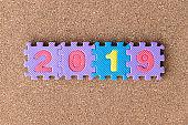 Foam alphabet puzzle in word 2019 on cork board background
