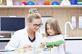 Child psychologist working with young girl in office