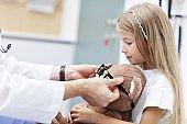 Child male optometrist examines eyesight of little girl