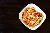 top view of kimchi in bowl on dark wooden table