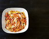 above view of kimchi in bowl on dark wooden board