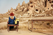 Travel. Woman Traveler In Hat With Backpack Travel To Cave Town