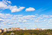 white clouds in blue sky over houses and park