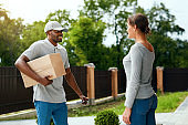 Package Delivering. Delivery Man Delivering Box To Woman