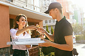 Food Delivery. Courier Delivering Pizza To Client Home