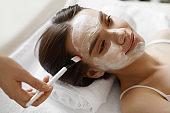Facial Beauty Treatment. Beautiful Woman Getting Cosmetic Mask