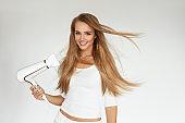 Hair Dryer. Woman Drying Beautiful Blonde Long Straight Hair