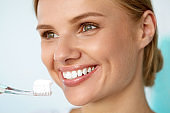 Beautiful Smiling Woman Brushing Healthy White Teeth With Brush