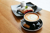Cup Of Coffee And Dessert At Table In Cafe