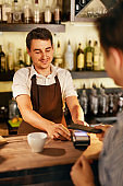 Customer Paying With Mobile Phone In Cafe